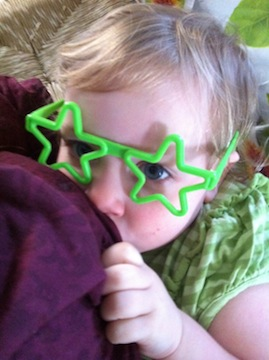Todller nursing wearing star-shaped sunglasses